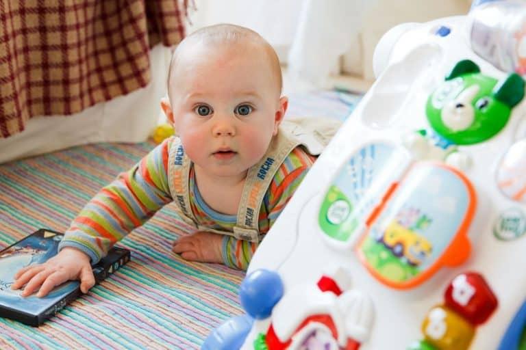 Baby spielt mit Spielbogen