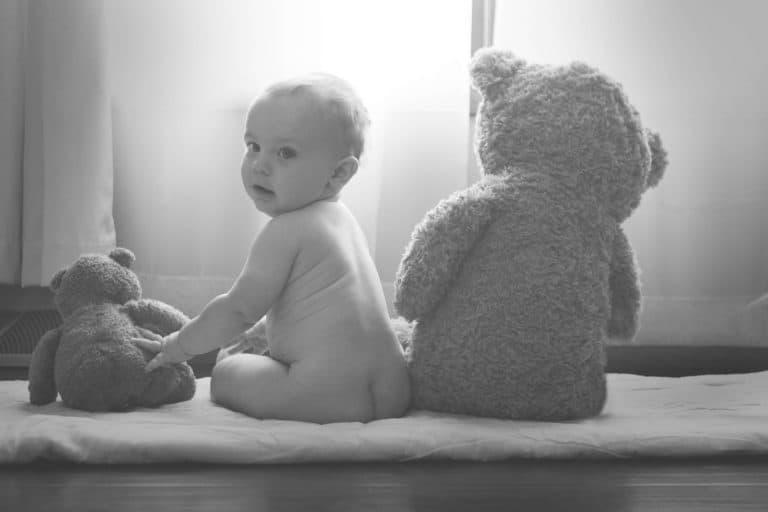 Baby mit Teddbybaer und Wickeltasche
