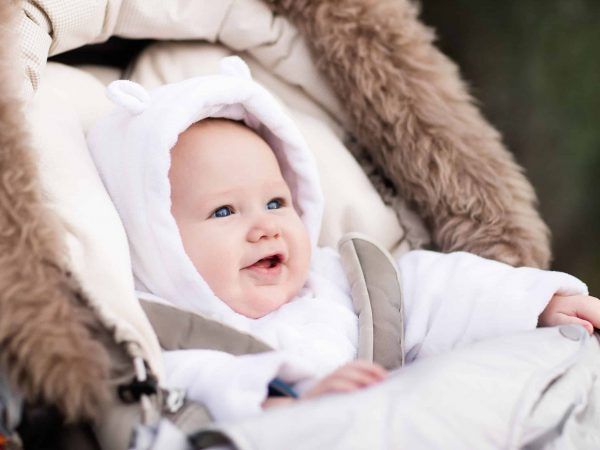 62520453 – happy laughing baby enjoying a walk in winter park sitting in a warm stroller with sheepskin hood