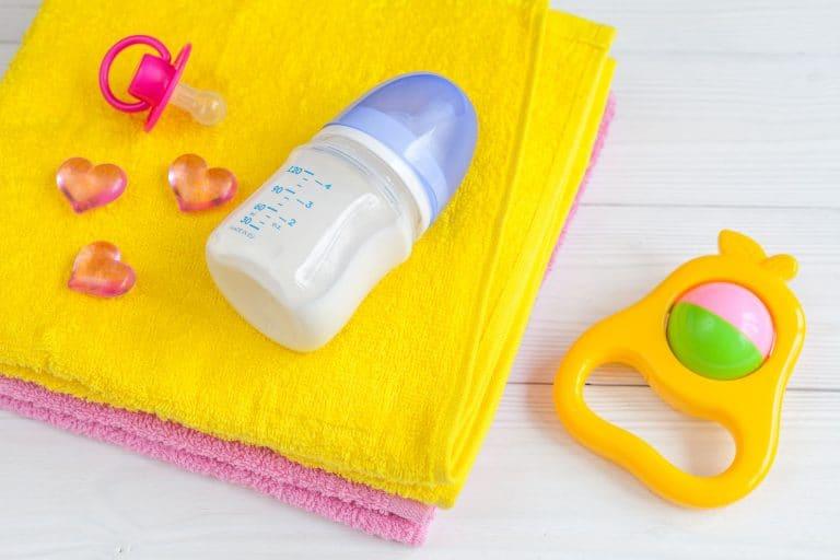 Babyflasche auf Handtuch mit Rassel
