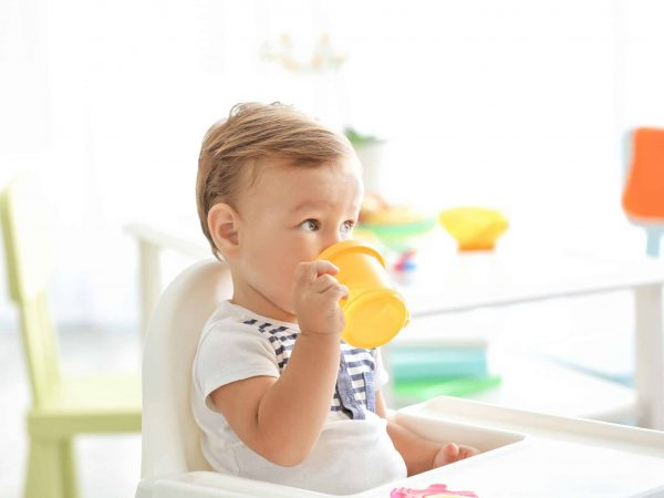 Adorable baby drinking from bottle while sitting in highchair at home