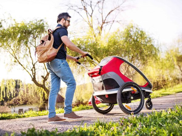 A father with backpack and jogging stroller on a walk outside in spring nature.
