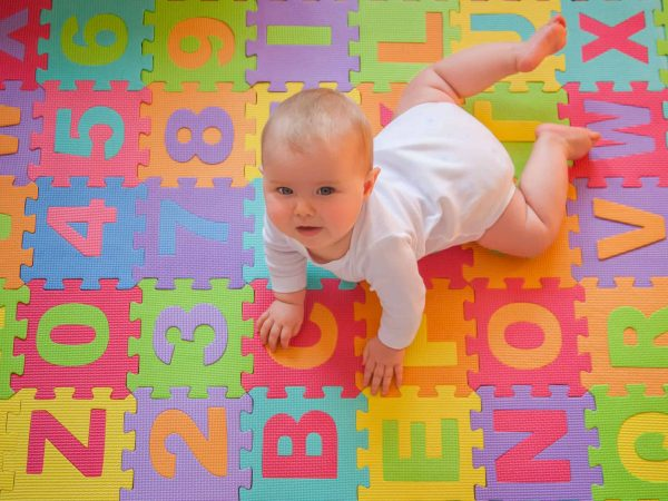 Cute baby looking up from colorful alphabet mat while playing on tummy.