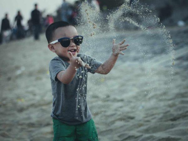 Kleinkind am Strand mit Sonnenbrille
