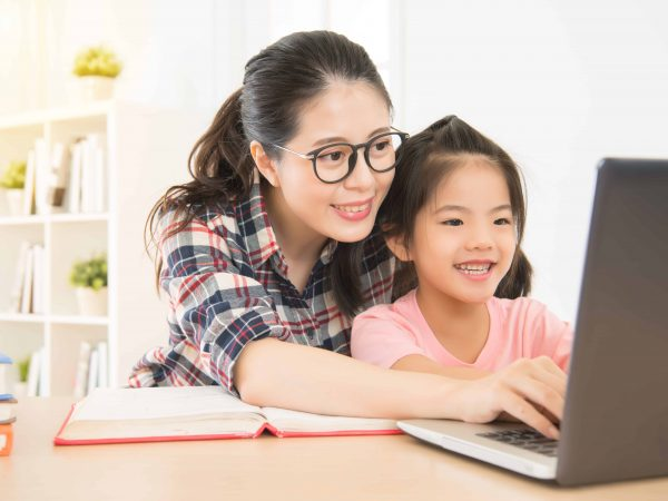 smile mother let her children know how to using laptop computer sitting in study room. happy girl excited in typing first time with her favorite mom.