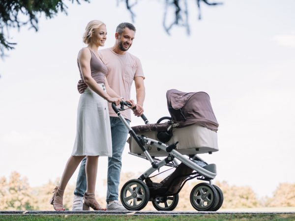 happy parents walking with baby carriage in park at weekend