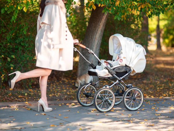 A slender girl in a light coat and high heels wheeling a stroller in the park.