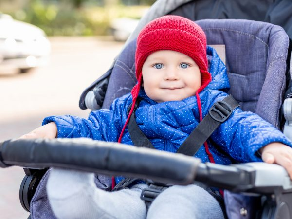 Cute little baby boy sitting in stroller and smiling during walk on cold autumn or winter day.Adorable kid wearing blue jacket and knitted red hat outdoors. Happy and healthy childhood concept.