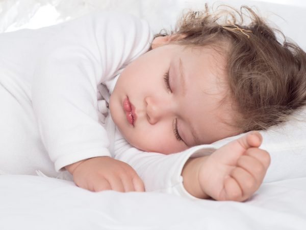 little adorable baby girl sleeping on bed