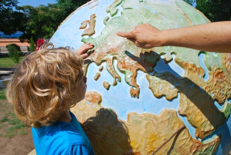 Kind greift und sieht auf großen Globus. Eine Hand zeigt nach Europa.