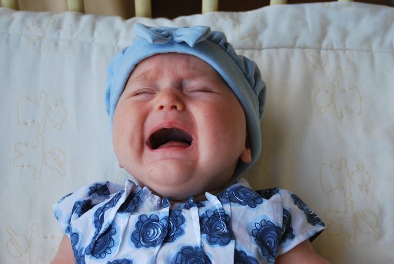 Ein Baby mit blauer Mütze und einem blauen Strampler, dass weint.