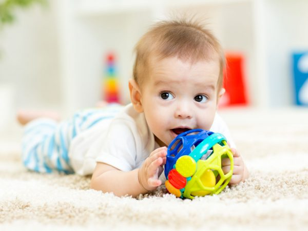 cute baby lying on soft carpet in children room